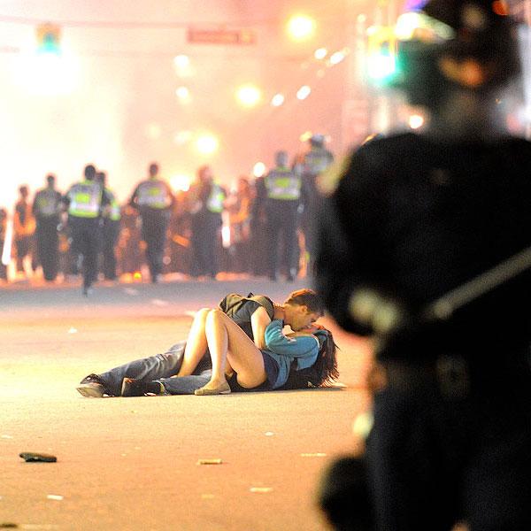 Casal se beija durante protesto após partida de hóquei no gelo em Vancouver.